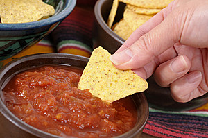 Mexican nachos and salsa with female hand