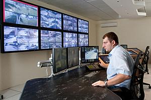 Man monitoring cctv cameras in modern control room